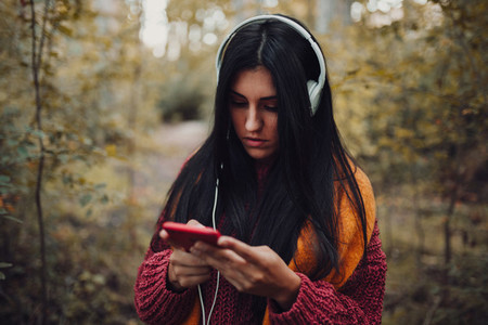 Young woman listening music with her headphones in the forest