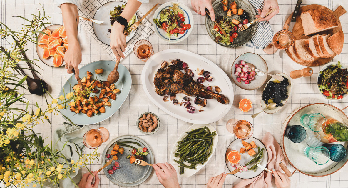 Peoples hands over table with meat  salads  wine  wide composition