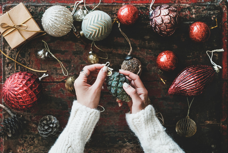 Christmas decoration toys and womans hands over red wooden background