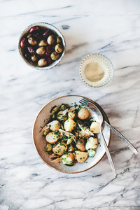 Greek lunch with potato salad and glass of white wine