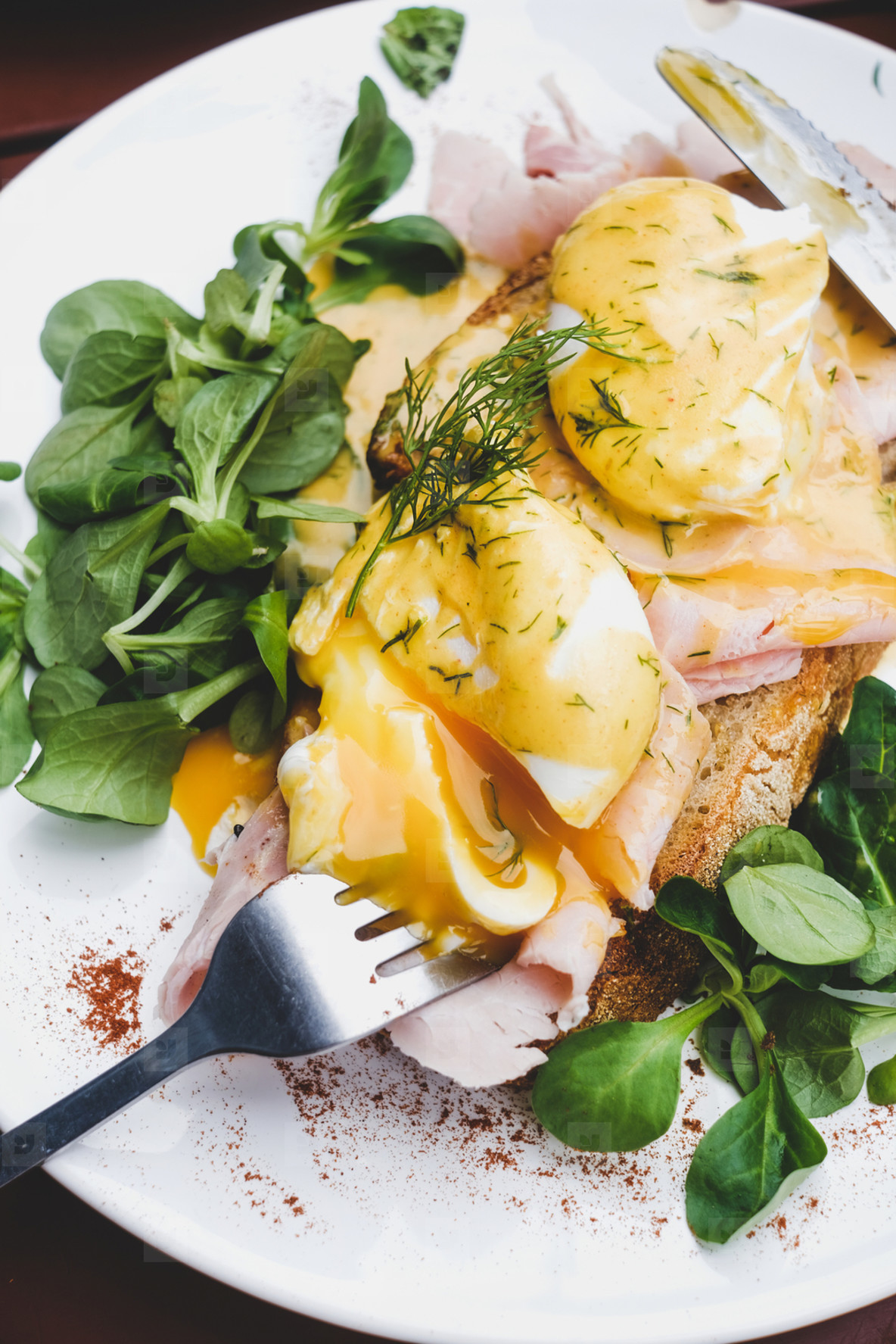 Poached eggs on sourdough bread with ham and salad