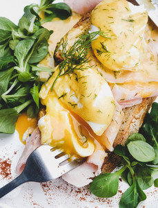 Poached eggs on sourdough bread with ham and green salad