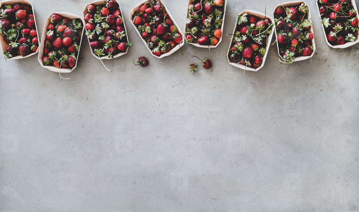 Fresh strawberries in plastic free boxes over grey background  copy space