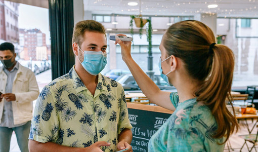 Business owner checking customers for fever