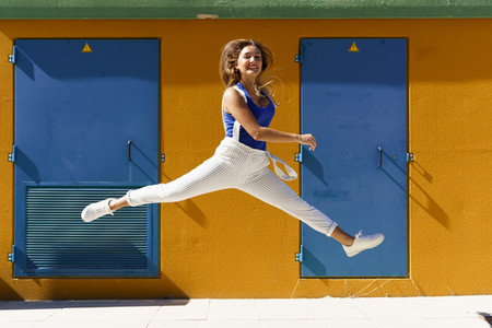 Happy young woman jumping in urban background