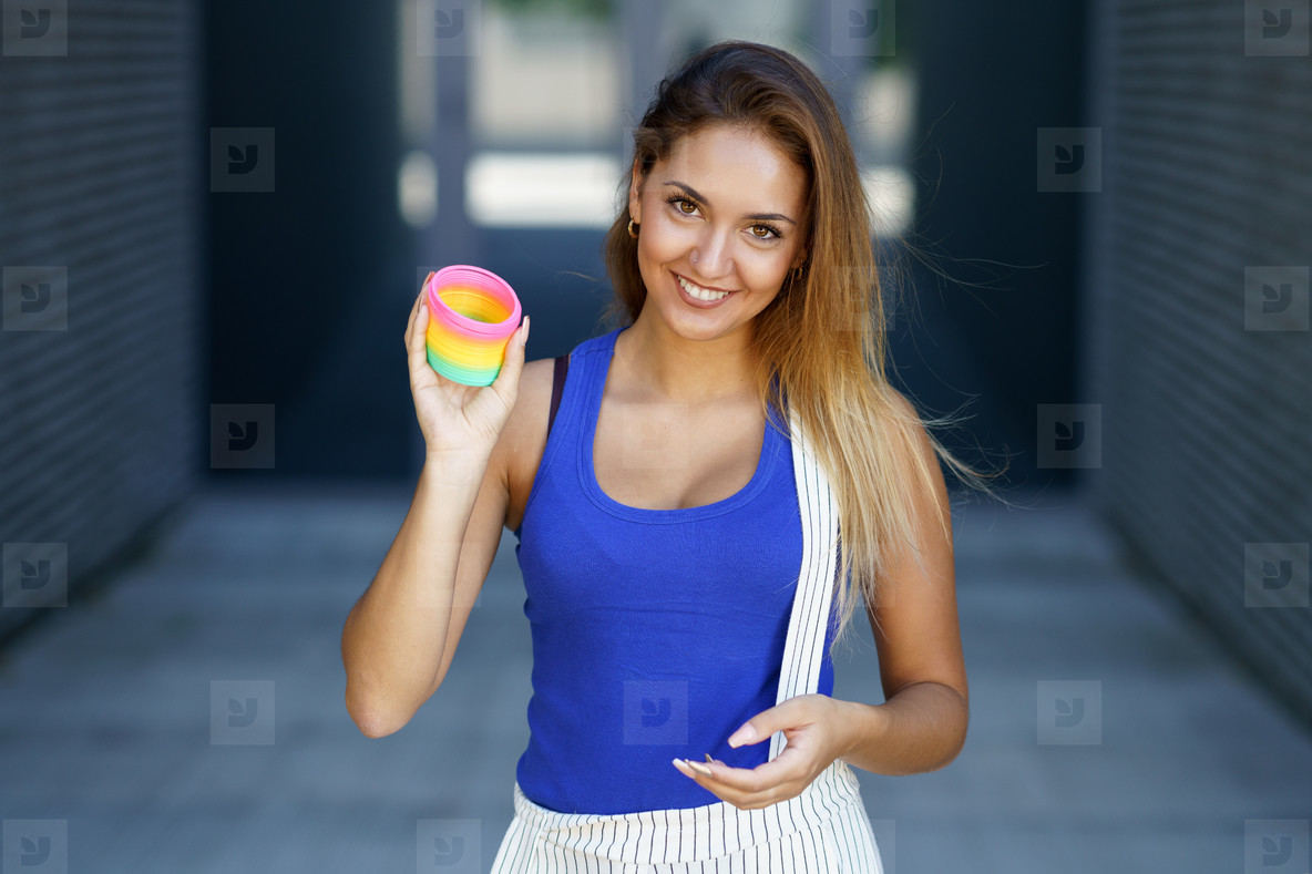 Girl playing with a colorful spring toy outdoors
