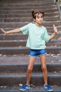 Nine year old girl dancing on the steps outdoors