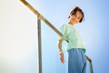 9 year old girl posing happily on a staircase