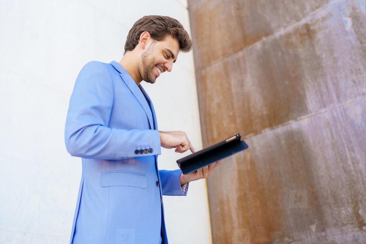 Businessman using a digital tablet near an office building