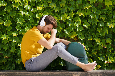 Young student sitting outside worried about his exams
