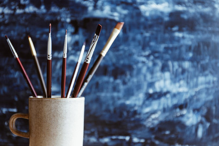 Painting brushes in a ceramic mug against a blue abstract background