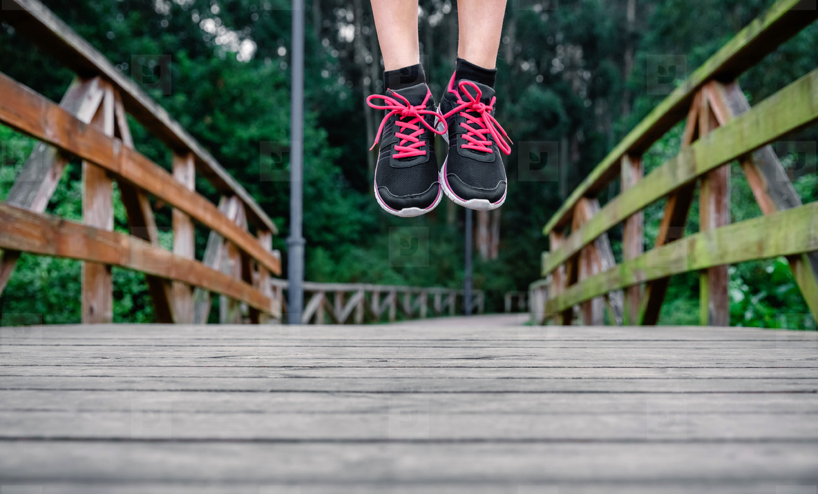 Athlete woman feet jumping outdoors