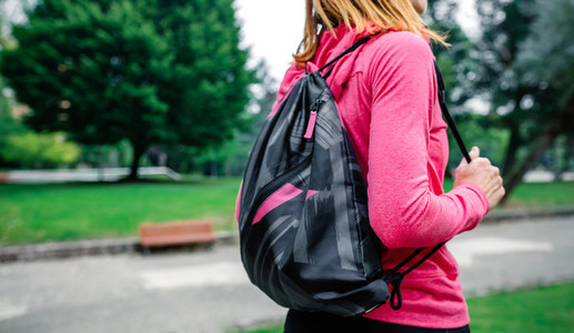 Unrecognizable sportswoman with backpack going to the gym