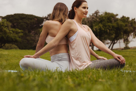 Two women friends sitting in park doing workout