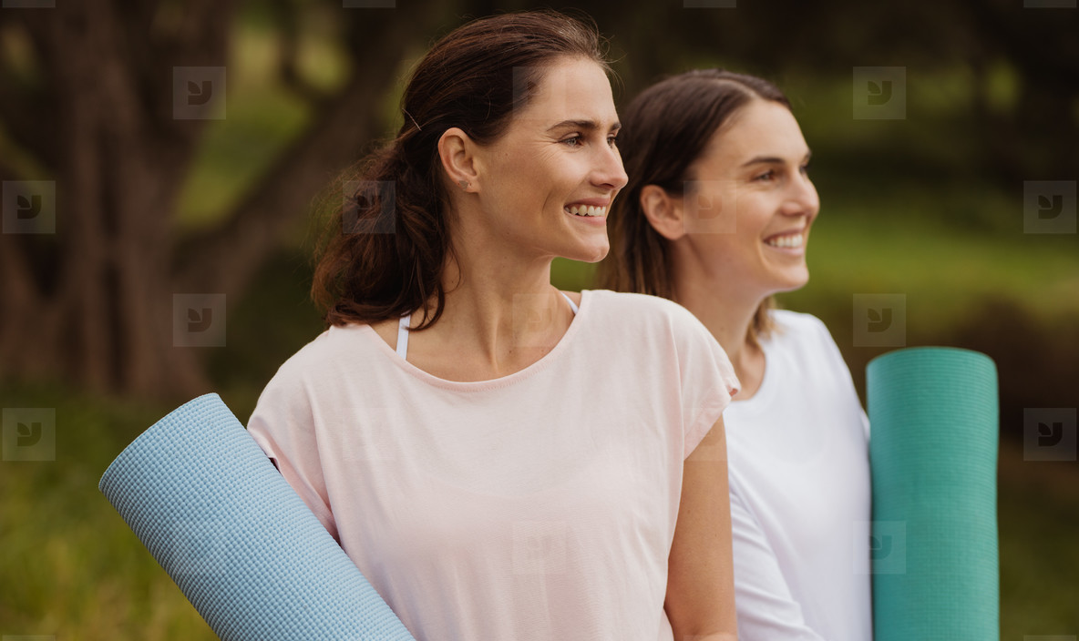 Fitness women standing outdoors holding yoga mats
