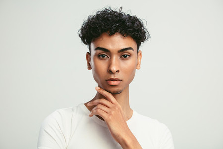 Portrait of an androgynous man on white background