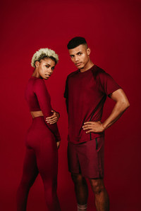 Portrait of fitness couple standing on maroon background