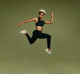 Athletic woman jumping in air
