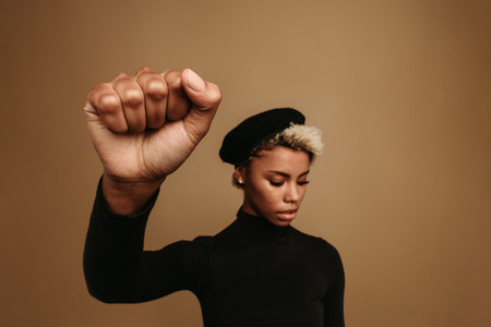 African american woman with raised fist on brown background