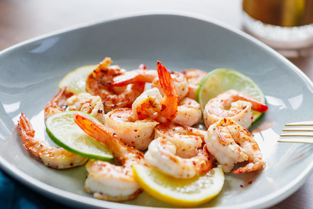 Fried tiger shrimp with lime  lemon and spices on a ceramic dish  Healthy dinner or lunch concept
