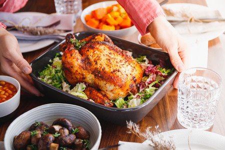 Hands put a dish with whole roasted chicken on a festive table  The concept of family dinner or Thanksgiving celebrate