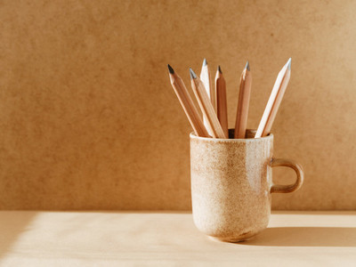 Pencils in a ceramic mug on a table with copy space