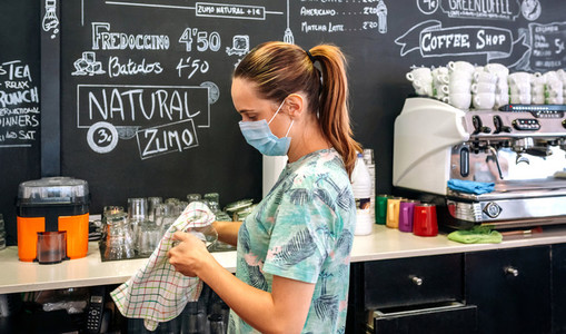 Waitress with mask cleaning glasses