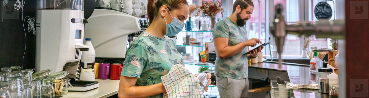 Waitress with mask cleaning glasses while her coworker works with tablet