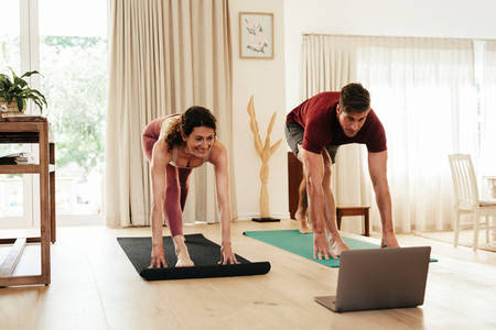 Couple exercising at home watching fitness video
