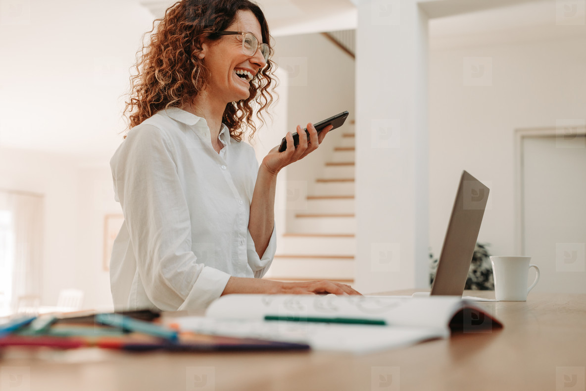 Happy businesswoman talking over phone at home