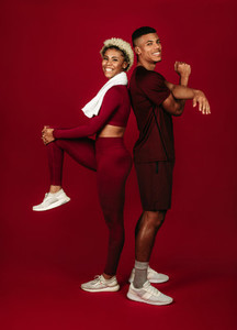 Cheerful fitness couple working out on maroon background