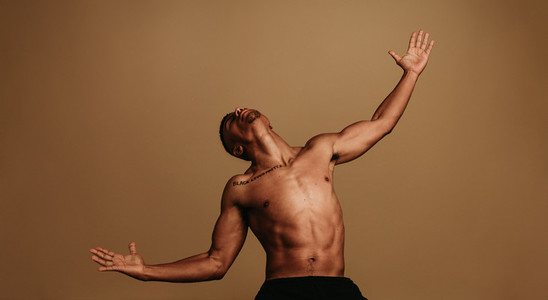 Portrait of muscular man with stretched arms