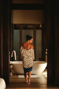 Woman walking in to a luxury spa for a bath