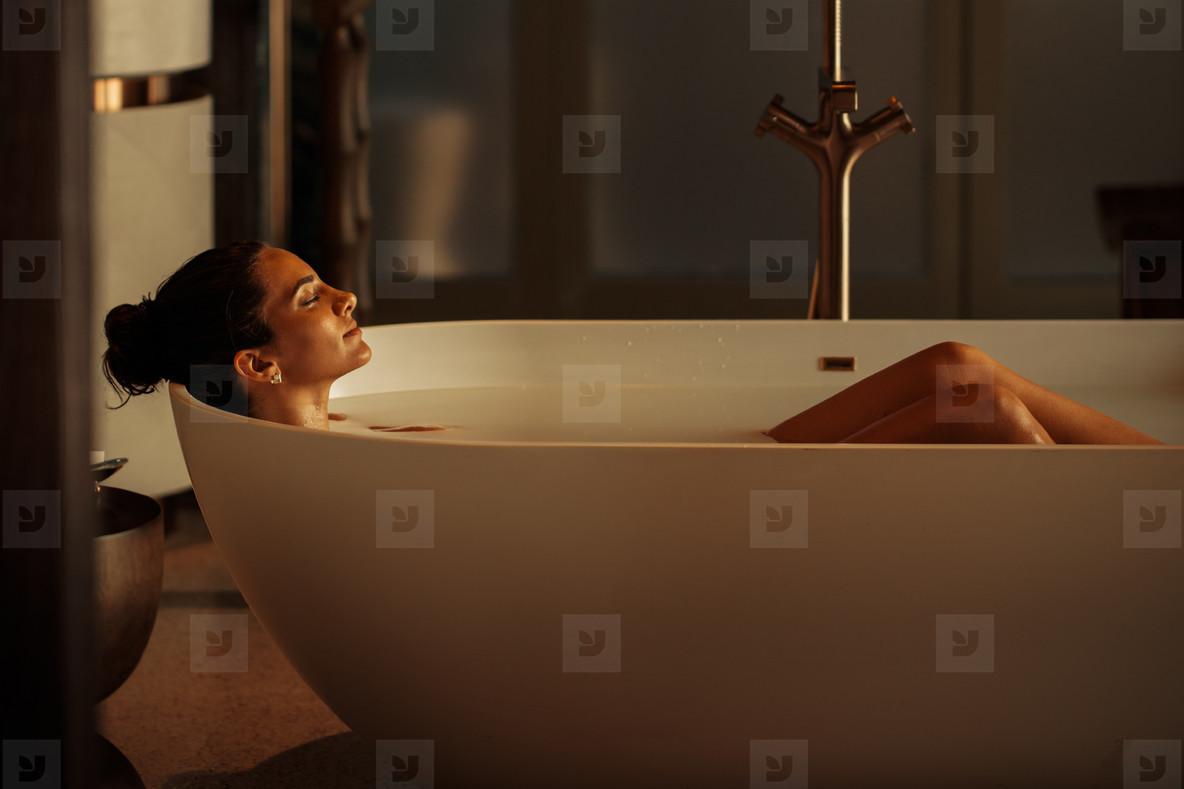 Woman lying in a luxury bathtub