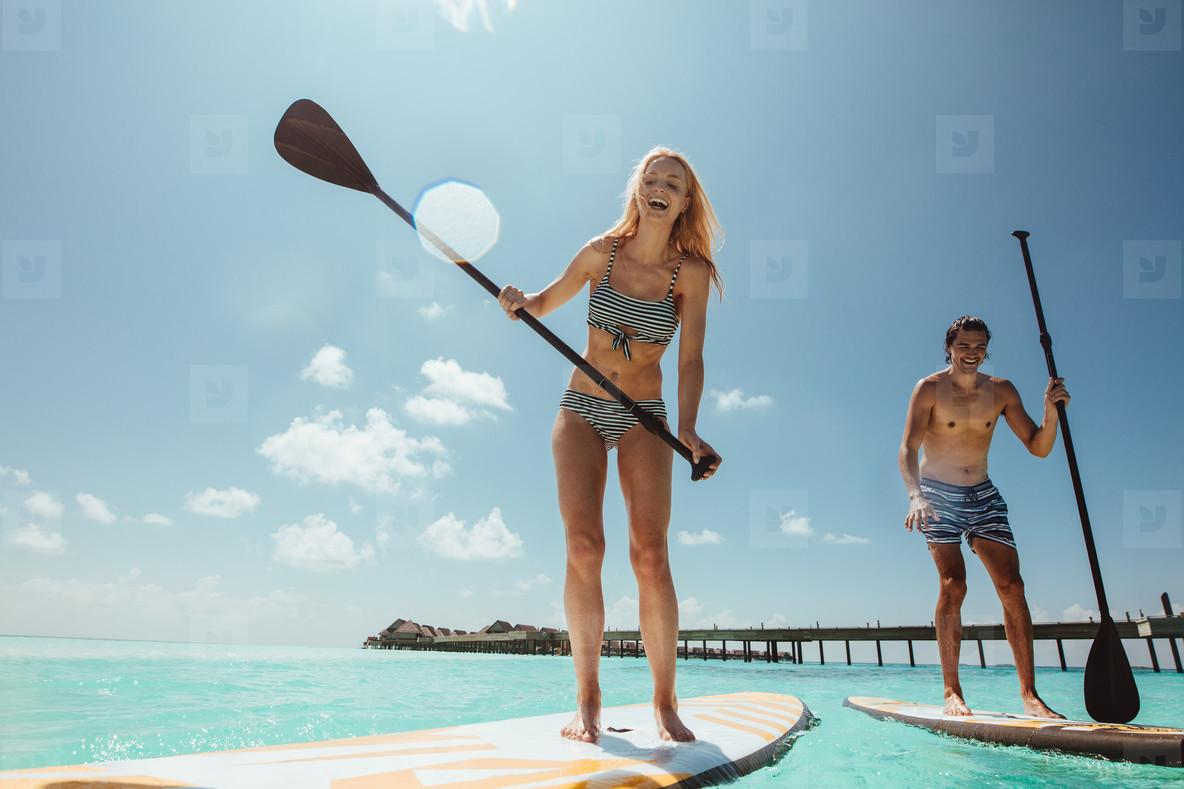 Couple having fun standup paddleboarding