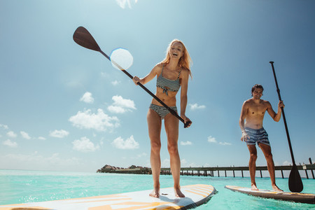 Couple having fun standup paddleboarding