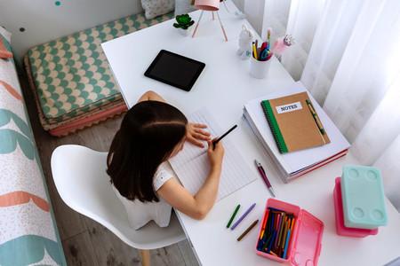Girl doing homework in her bedroom