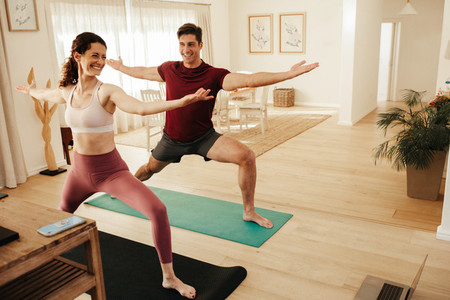 Couple exercising watching online fitness tutorial