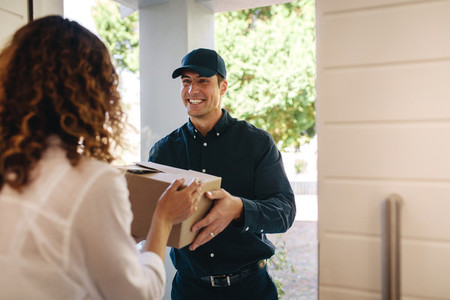 Courier worker delivering a parcel to woman