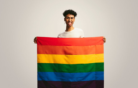 Gay man with pride flag making funny face
