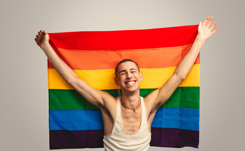 Smiling transgender man with pride flag
