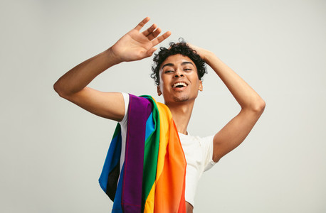 Cheerful gay man with lgbt flag