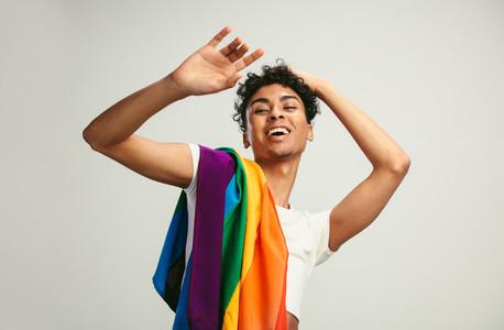 Cheerful gay man with lgbt flag