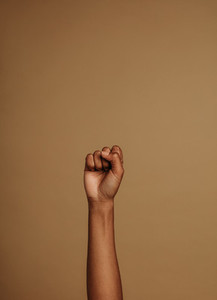 Raised hand on brown background