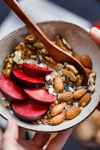 Hands hold a morning dish with oat flakes  plum  almond and walnut