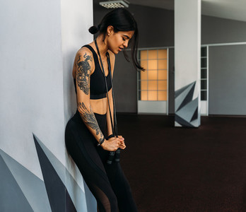 Muscular woman leaning to wall