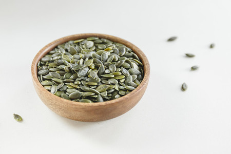 Pumpkin shelled dried seeds or pepitas in a wooden bowl Healthy additive concept
