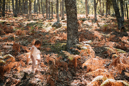 Little caucasian baby girl squatting in the forest among ferns
