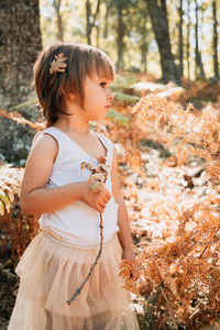 Little caucasian baby girl standing in the forest among ferns