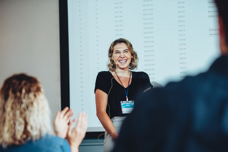 Businesswoman getting a round of applause after successful prese